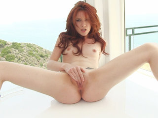 Redhead Elle Alexandra toys with her little tits..